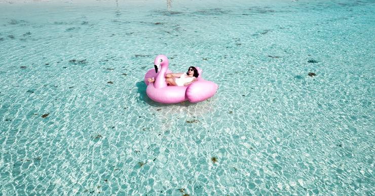 woman-lying-on-pink-flamingo-bouy-on-body-of-water-1267051