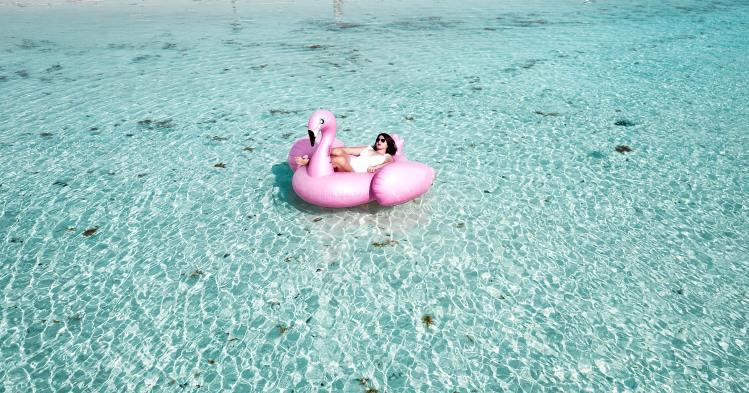 woman-lying-on-pink-flamingo-bouy-on-body-of-water-1267051
